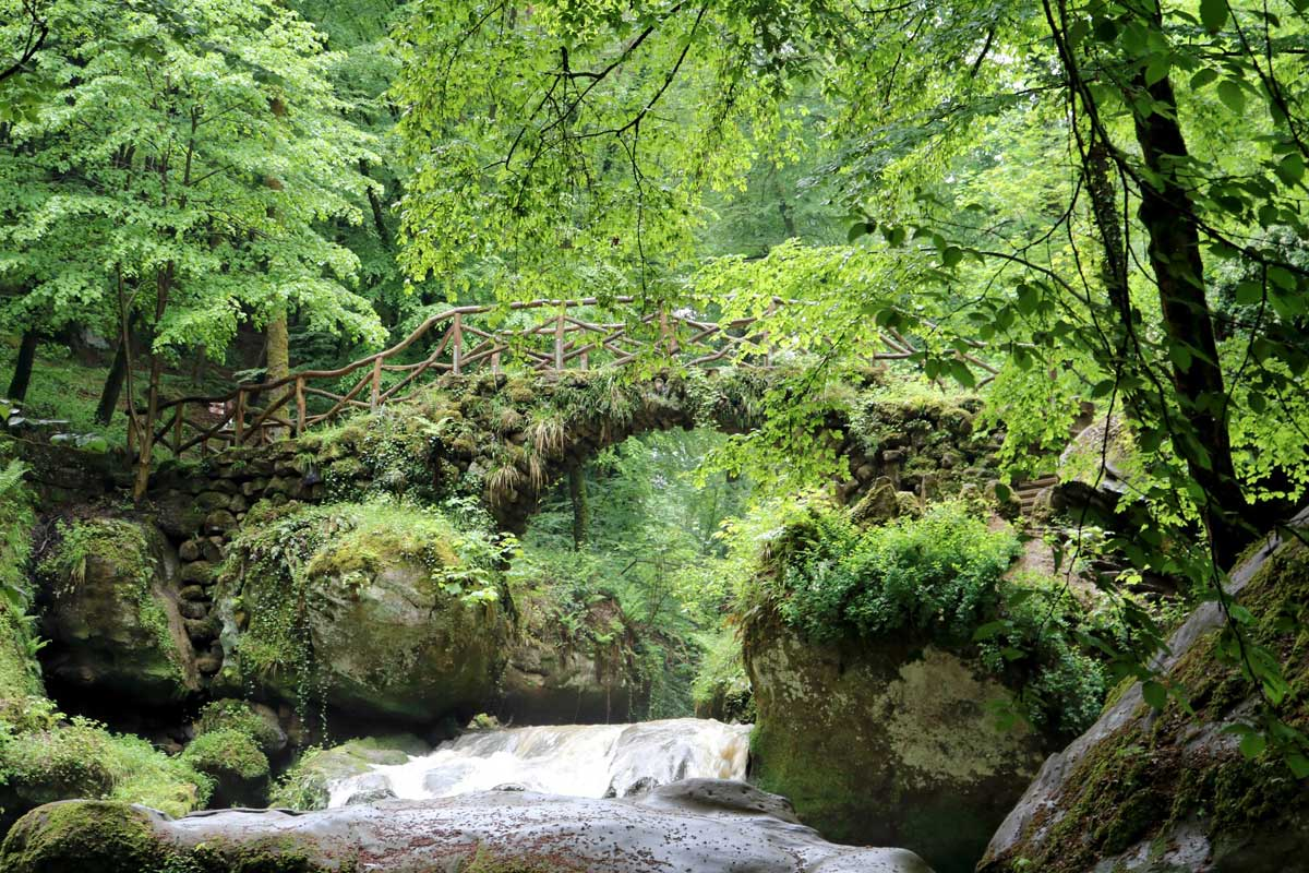 moss covered bridge on mullerthal trail in luxembourg